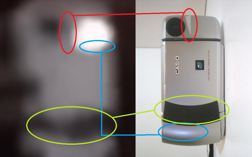 L'angolo scuro (segnato nel cerchietto rosso) combacia con l'angolo della parte superiore quadrata della Casio QV-100, inoltre il bagliore celestino cerchiato in blu è simile al bagliore di un riflesso presente nella foto della QV - 100: elementi che lasciano intuire che potrebbe trattarsi di un riflesso. In verde la fascia argentata è presente in entrambe le foto e combacia con il design della QV - 100.